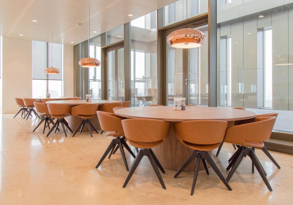 Ronde tafels van notenfineer met sokkelpoot.