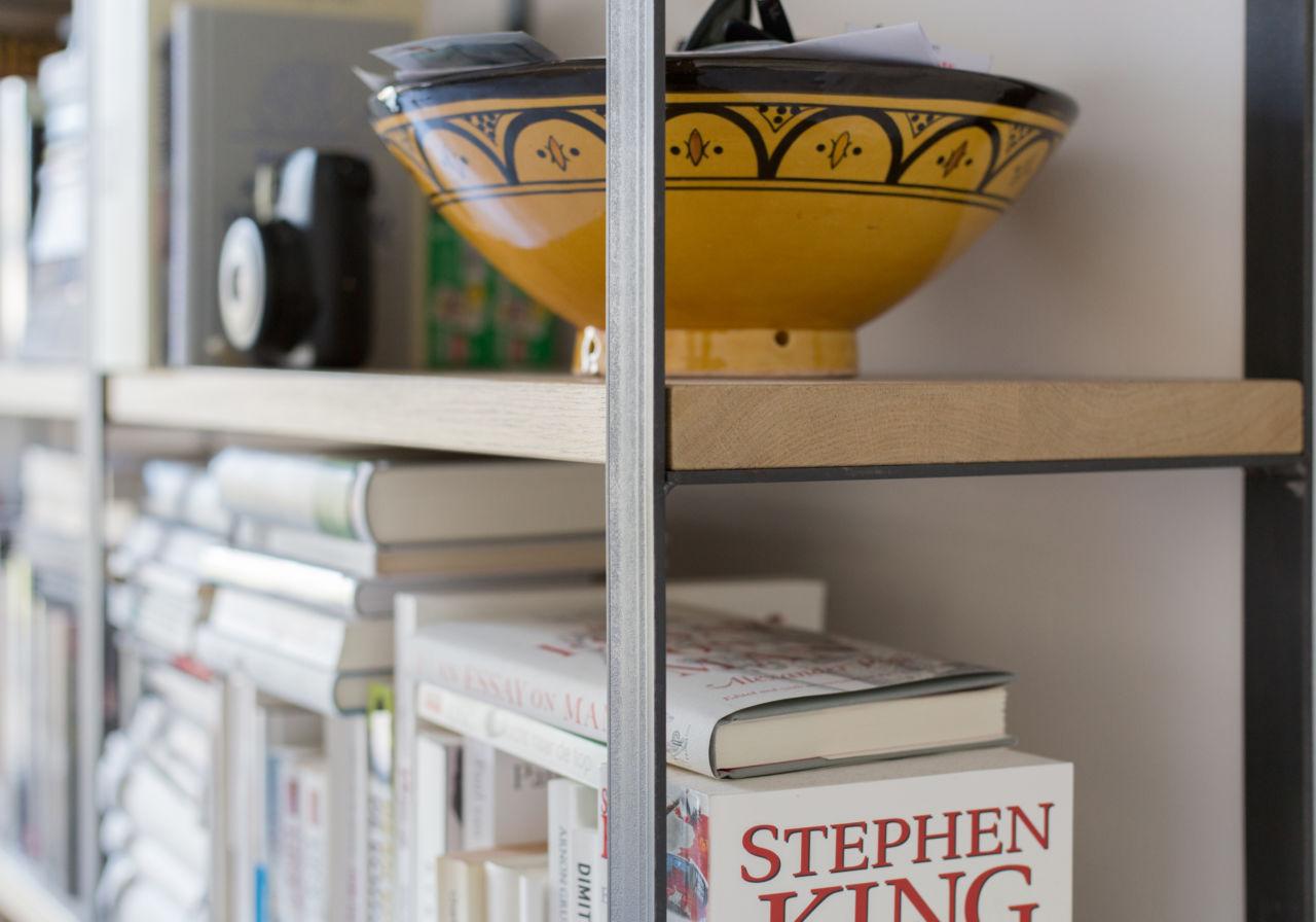 Detail boekenkast van staal en eikenhout.